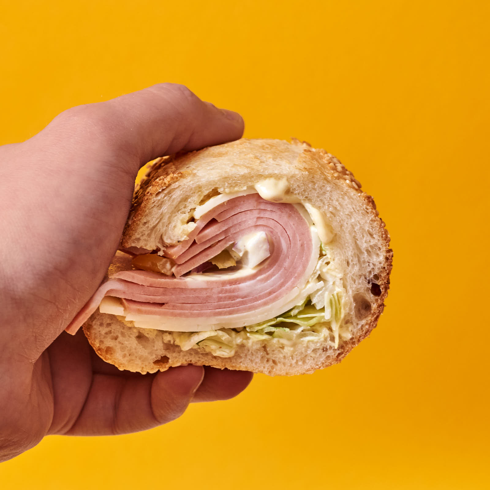 A seeded and scooped-out hoagie roll from this recipe with mortadella, sharp provolone, red onion, shrettuce, dijonaise, and pickled hot banana peppers.