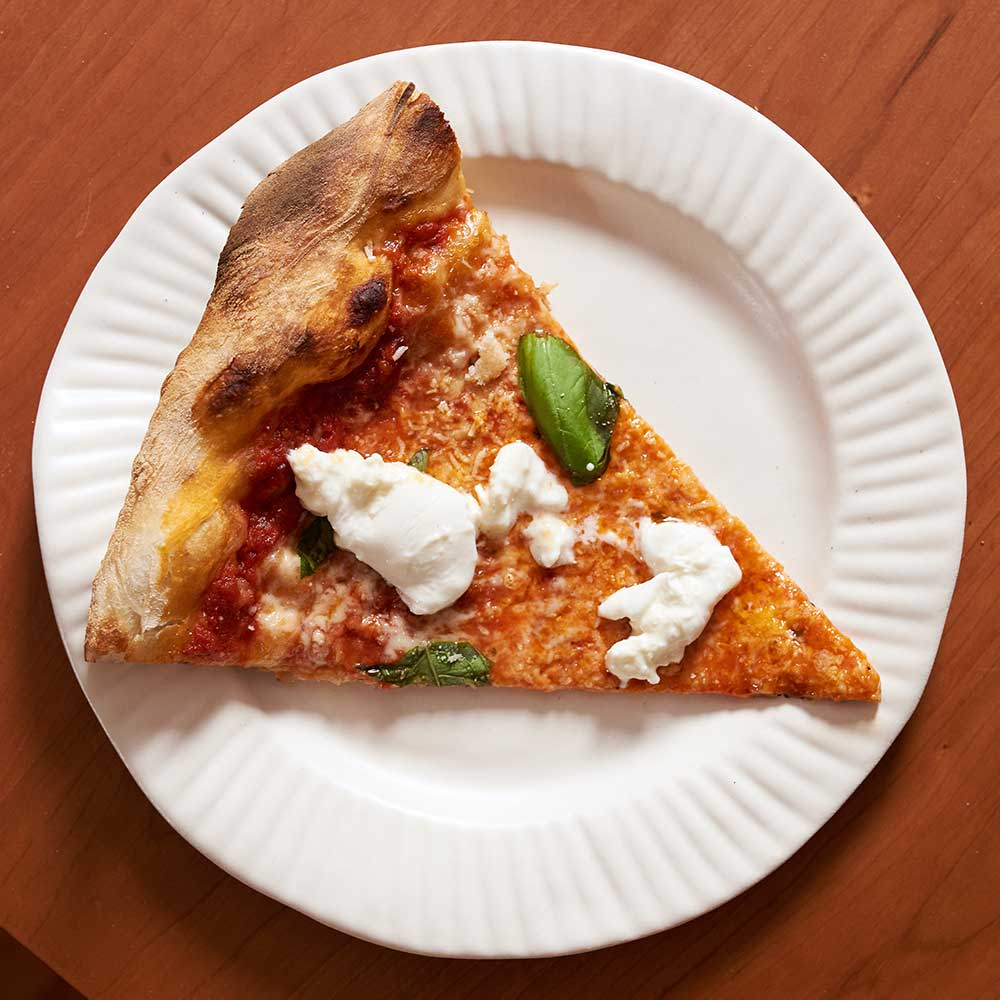 Pizza with aged mozzarella, tomato sauce, and Parmesan Reggiano, with burrata, basil and Parmesan Reggiano added post-bake, inspired by L'industrie Pizzeria's burrata slice. Baked in a commercial deck oven.