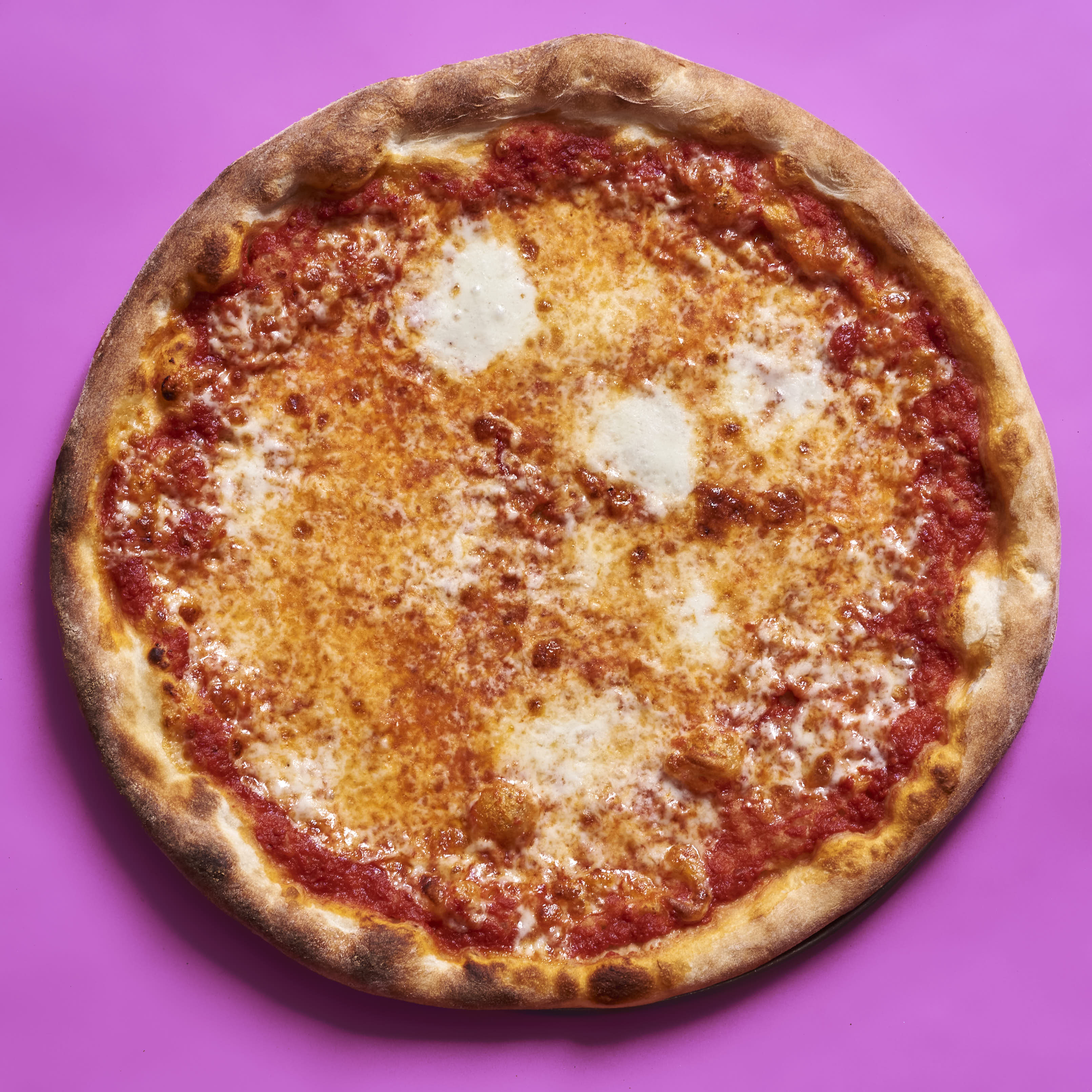 A pizza with tomato sauce, aged mozzarella, and fresh mozzarella. Baked in a typical home oven on a 3/8-inch-thick steel plate.