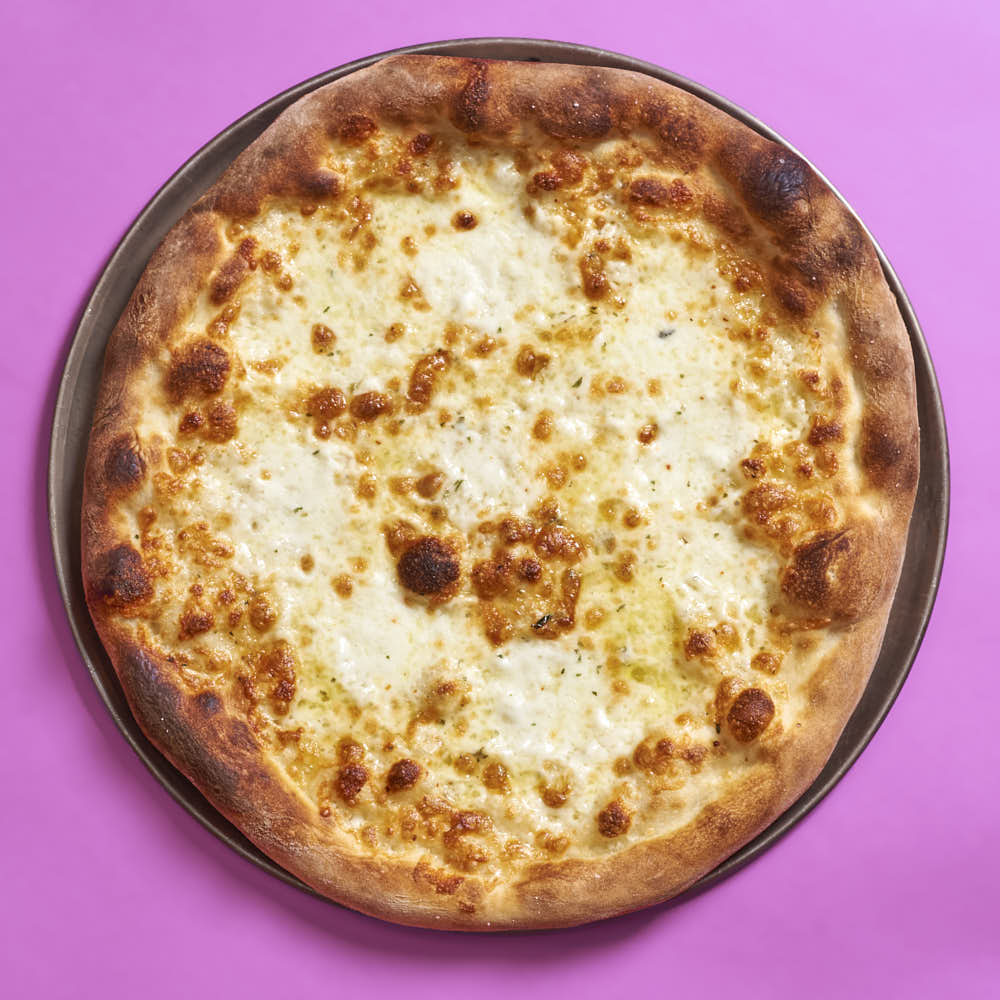 A white pizza with aged mozzarella, fresh mozzarella, and oregano. Baked in a typical home oven on a 3/8-inch-thick steel plate.