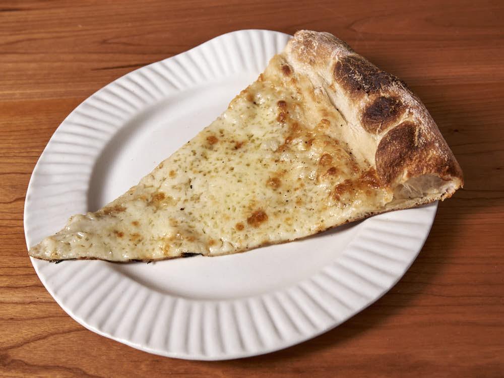 Pizza with aged mozzarella, fresh mozzarella, and Parmesan Reggiano, Pecorino Romano, Tellicherry pepper, and dried oregano. Baked in a commercial deck oven.